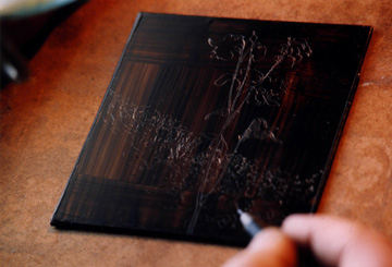 image of David Ladmore drawing into a hardground covered  copper plate to expose the copper in preparation for etching